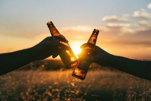 Two people holding beer bottles.