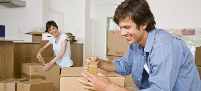 man and woman packing boxes with Longmont movers