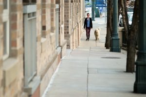 A woman walking a dog in one of the best neighborhoods in Denver.
