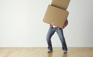 man holding boxes he needs to unpack as one of the first things to do in Arvada after the move
