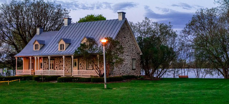 A beautiful cobblestone house on a dark green grass lawn at dusk; Thornton CO movers can make your residential dreams a reality!