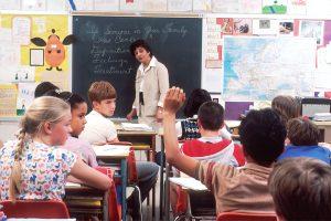 Children in a classroom with a female teacher