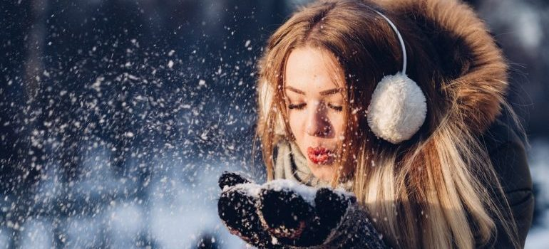 A woman blowing snow
