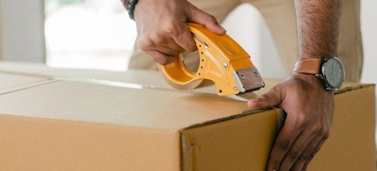 man sealing the moving box