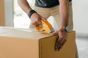 Man taping shut a box