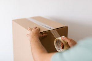 Man sealing a carton box to pack properly
