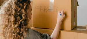 """Woman labelingbrown box with """"fragile"""" sign"""