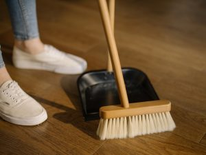 person sweeping a wooden floor