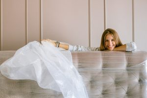Woman wrapping her couch and applying one of the tips for moving during the winter