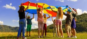 kids playing under a colorful tarp