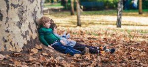 two children sitting under a tree