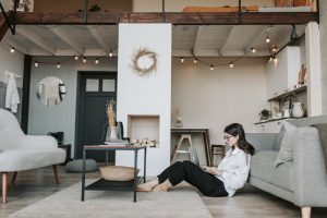 woman sitting on a floor of the apartment with a laptop