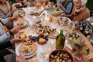 neighbors enjoying a meal together at the same table after hosting a garden party