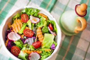 a picture of a salad from above with a bottle of vinegar next to it