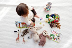 an infant playing with various toys around him