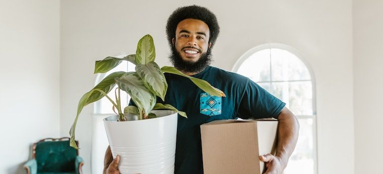 man holding a box and flowers is part of moving services Denver