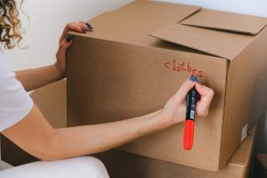 A woman writing on her moving box