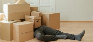 man laying on the floor covered in moving boxes apparently overwhelmed by moving