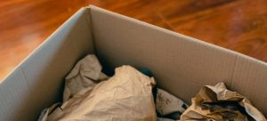 packing a moving box using plain paper for protection