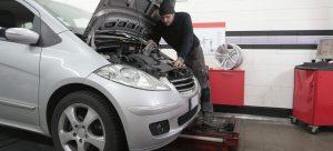 A man is inspecting car fluids.