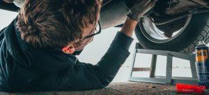 A mechanic is repairing a car.