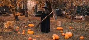 Masked girl with pumpkins and a broom.