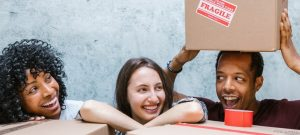 two girls and a guy playing with packing materials